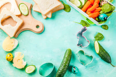 Cooking creative kids breakfast lunch box for Easter, sandwiches with cheese, fresh vegetables - cucumbers, carrots, spinach, colorful quail eggs. Light blue table, copy space top view frame Stockfoto