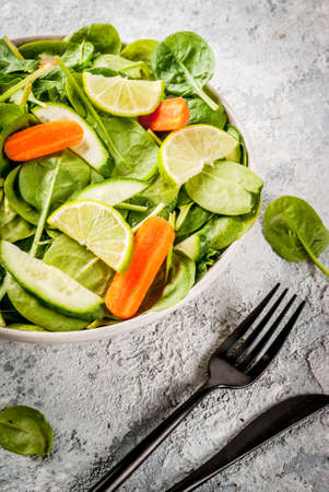 Diet plan weight lose concept, fresh vegetable salad with fork, knife, grey stone table copy space