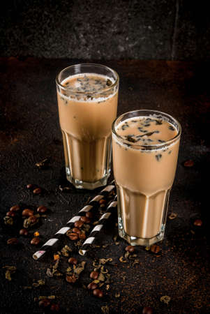 Asian, Malaysian traditional drink Yuenyeung from tea, coffee, milk, with ice cubes, on dark rusty background copy space