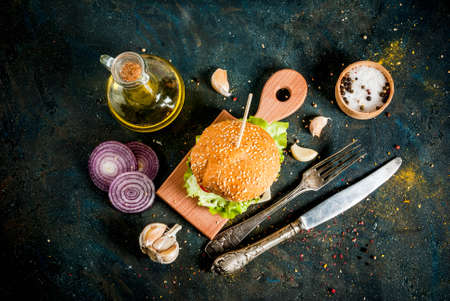 Fast food. Unhealthy food. Delicious Fresh Tasty Burger with Beef Cutlet, fresh Vegetables and Cheese on dark blue concrete background. Copy space top view Stockfoto