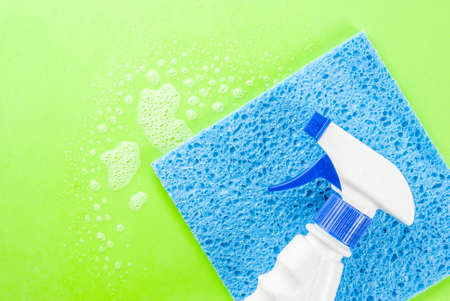 Spring cleaning concept Cleaning spray, sponges with foam on green background copy space