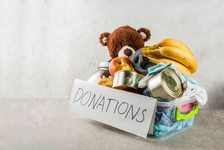 Plastic donation box with toys, clothes and food, white grey background copy space Stockfoto