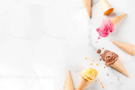 Homemade chocolate, vanilla, berry ice cream in ice cream cones, white marble background copy space top view