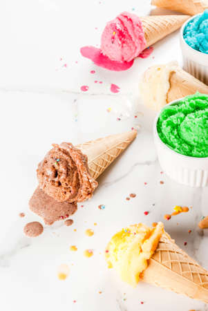 Different homemade melting ice cream in bowls and waffle ice cream cones, white vanilla, orange, pink berry, green, blue, chocolate white marble background  copy space
