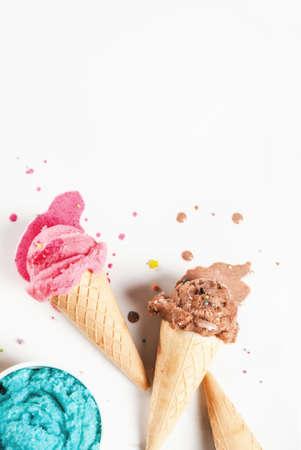 Homemade berry and chocolate ice cream in waffle cones, white marble background copy space top view