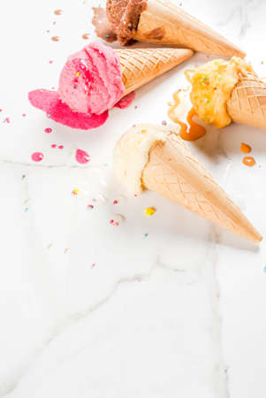 Homemade berry vanilla caramel chocolate ice cream in waffle cones, white marble background copy space