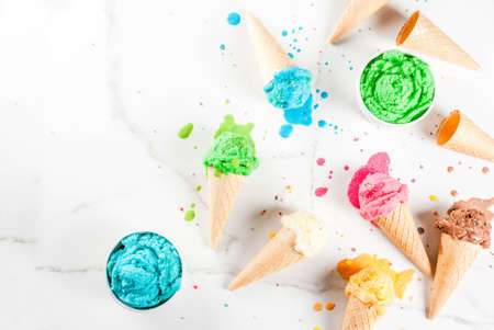 Different homemade melting ice cream in bowls and waffle ice cream cones, white vanilla, orange, pink berry, green, blue, chocolate white marble background  copy space top view Archivio Fotografico