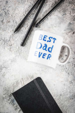 Fathers Day concept, background for congratulating cards with a cup with the inscription Best Father ever, business notebook and pencils. copy space top view Archivio Fotografico