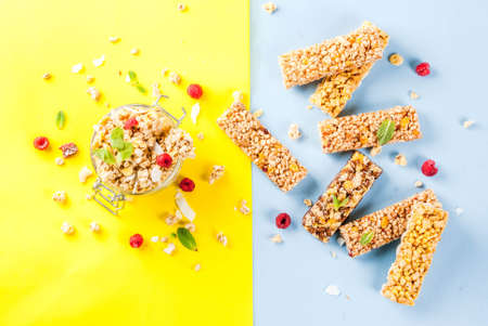 Healthy breakfast and snack concept, homemade granola with fresh raspberries and nuts in jar and granola bars, on bright yellow and blue background copy space seamless pattern Archivio Fotografico