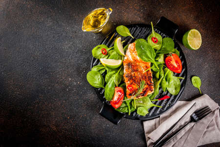 Grilled salmon steak filet with fresh vegetables, spinach and lime, dark rusty table top view copy space Archivio Fotografico