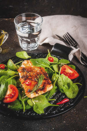 Grilled salmon steak filet with fresh vegetables, spinach and lime, dark rusty table copy space Archivio Fotografico