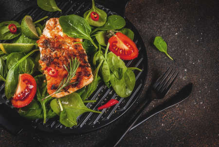 Grilled salmon steak filet with fresh vegetables, spinach and lime, dark rusty table copy space top view Archivio Fotografico