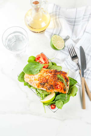 Grilled salmon steak filet with fresh vegetables, spinach and lime, white marble table copy space Foto de archivo