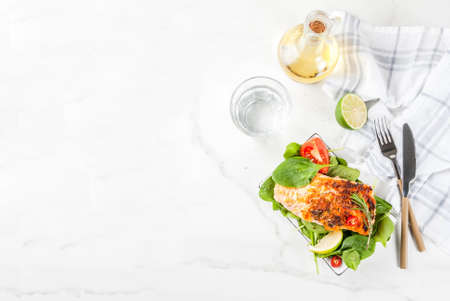 Grilled salmon steak filet with fresh vegetables, spinach and lime, white marble table copy space top view