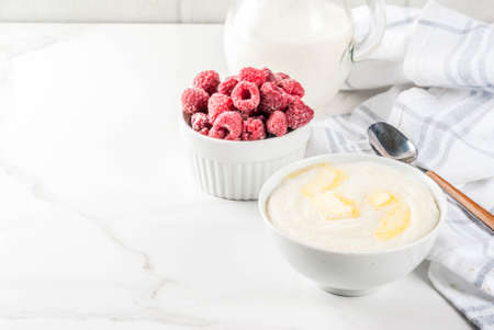 Healthy breakfast, semolina porridge with milk and raspberry, white marble table copy space