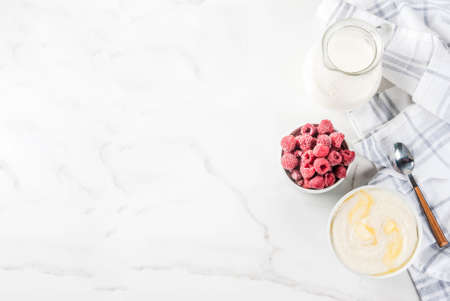 Healthy breakfast, semolina porridge with milk and raspberry, white marble table copy space top view Archivio Fotografico
