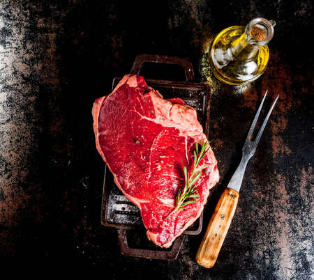 Fresh raw meat, lamb beef marble steak on a grill pan board, with ingredients for cooking. On dark rusty metal table, copy space top view Archivio Fotografico