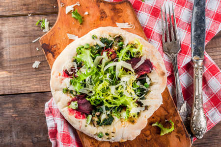 Vegan pizza with fresh vegetables and pesto, wooden background, copy space top view