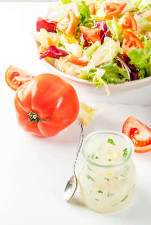 Classic salad dressing, homemade ranch dressing with olive oil herbs and lemon, with fresh vegetables on white marble table, copy space Archivio Fotografico