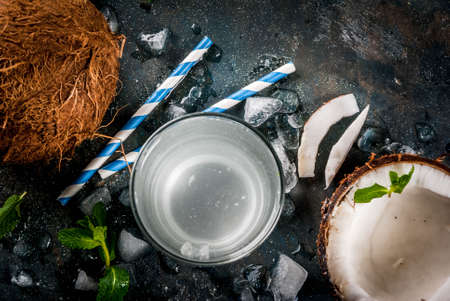 Healthy food concept.  Fresh Organic Coconut Water with coconuts, ice cubes and mint, on rusty dark blue background, copy space top view Archivio Fotografico