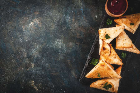 Asian food. Vegetarian samsa (samosas) with tomato sauce. Dark blue background copy space top view Archivio Fotografico