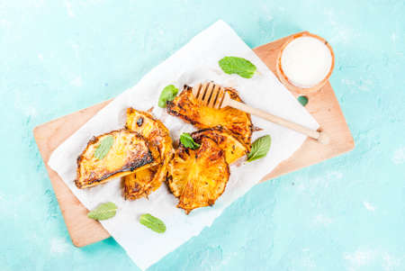 Grilled pineapple slices with mint, Honey and lime sauce, on light blue background copy space top view Archivio Fotografico