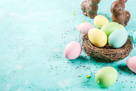 Multicolored Easter eggs with decorative birds nest and sugar sprinkles on a light blue background,copy space Archivio Fotografico
