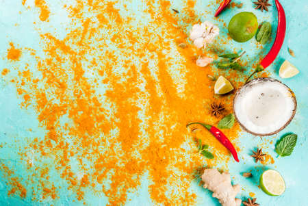 Asian and thai food, cooking background. Spices and ingredients - coconut, ginger, hot red peppers, lime, curry, mint, spices. Light blue background. Top view copy space