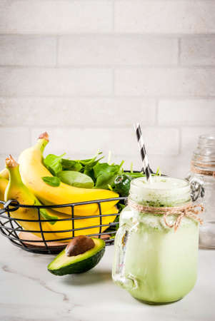 Healthy smoothie with banana and baby spinach, n white marble background copy space