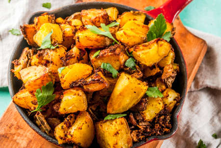 Indian food, Bombay Potatoes on light blue background copy space Stock Photo