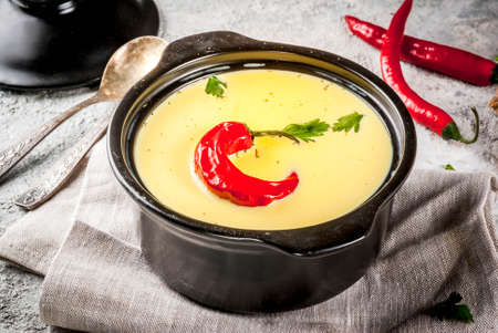 Traditional Indian cuisine. Vegetarian curry Gujarati Kadhi, Gujarati daal soup, with spices on grey stone background copy space