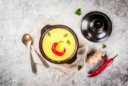 Traditional Indian cuisine. Vegetarian curry Gujarati Kadhi, Gujarati daal soup, with spices on grey stone background copy space top view