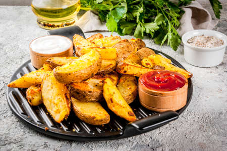 baked fried potatoes with garlic, herbs, red and white sauces, on grey stone background copy space Zdjęcie Seryjne