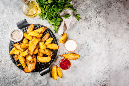 baked fried potatoes with garlic, herbs, red and white sauces, on grey stone background copy space top view