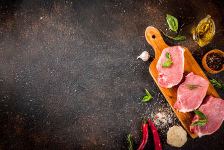 Raw meat, pork steaks with spices, herbs, olive oil, dark background top view, copy space 版權商用圖片