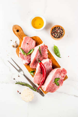 Raw meat, pork steaks with spices, herbs, olive oil, white marble background on cutting board, top view, copy space Фото со стока