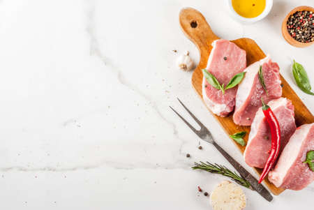 Raw meat, pork steaks with spices, herbs, olive oil, white marble background on cutting board, top view, copy space Stock Photo