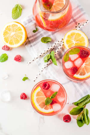 Summer refreshing drinks, fruit and berry raspberry mojito or lemonade with fresh mint, frozen raspberries, slices of lemon, ice, on a light background. copy space top view Reklamní fotografie