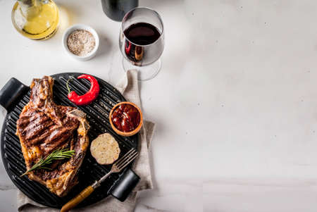 Fresh grilled meat beef steak with with red wine, herbs and spices. Top view copy space white marble background Banco de Imagens