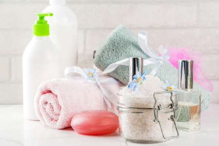Spa relax and bath concept, sea salt, soap, with cosmetics and towels in bathroom white background, copy space Stock Photo