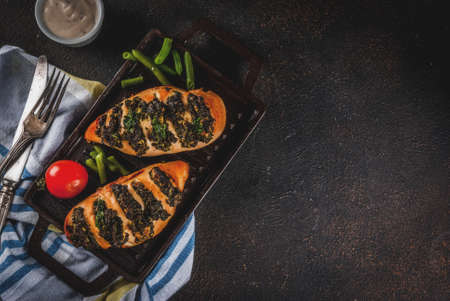 Healthy dinner, Pollo a fisarmonica con ricotta e spinaci, chicken fillet baked with cheese and spinach. On grill pan, with sauce and fresh vegetables.  top view copy space Foto de archivo - 98166069