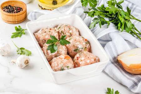 De ruwe eigengemaakte vleesballetjes van kip of van Turkije in bakselschotel op witte marmeren achtergrond. Kopieer ruimte.
