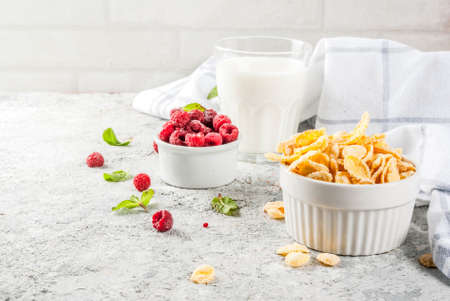 Healthy breakfast ingredients. Breakfast cereal flakes, milk or yogurt glass, raspberries and mint on grey stone background, copy space