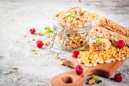 Healthy breakfast and snack concept, homemade granola with fresh raspberries in jar and nuts and granola bars, on grey stone stone background copy space