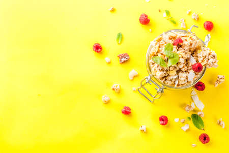 Healthy breakfast and snack concept, homemade granola with fresh raspberries in jar, on bright yellow background copy space  top view Stok Fotoğraf
