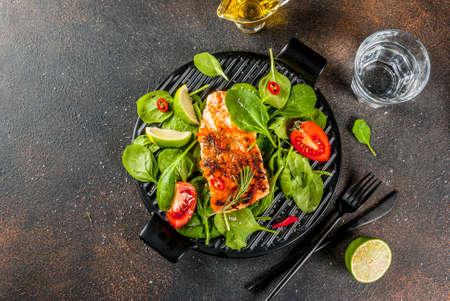 Grilled salmon steak filet with fresh vegetables, spinach and lime, dark rusty table copy space top view Stock Photo