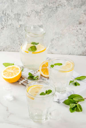 Summer refreshing drinks, mojito or lemonade with fresh mint, slices of lemon, ice, on a light background. copy space