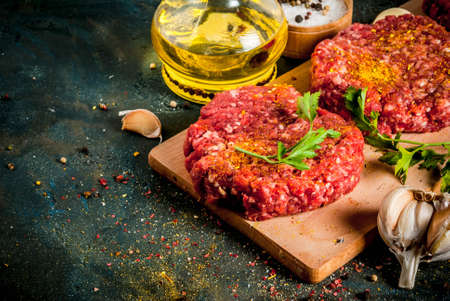 Raw burger cutlets with salt, pepper, oil, herbs and spice, on dark table, copy space Stock Photo