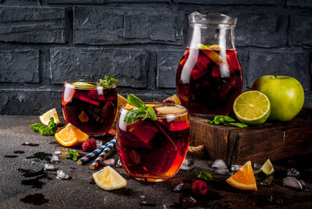 Summer cold cocktail, fruit and berry red wine sangria with apple, lemon, oranges and raspberry. dark background, copy space