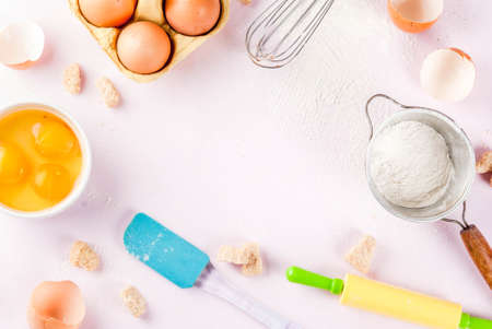 Ingredients and utensils for cooking baking egg, flour, sugar, whisk, rolling pin, on light pink background, copy space top view frame